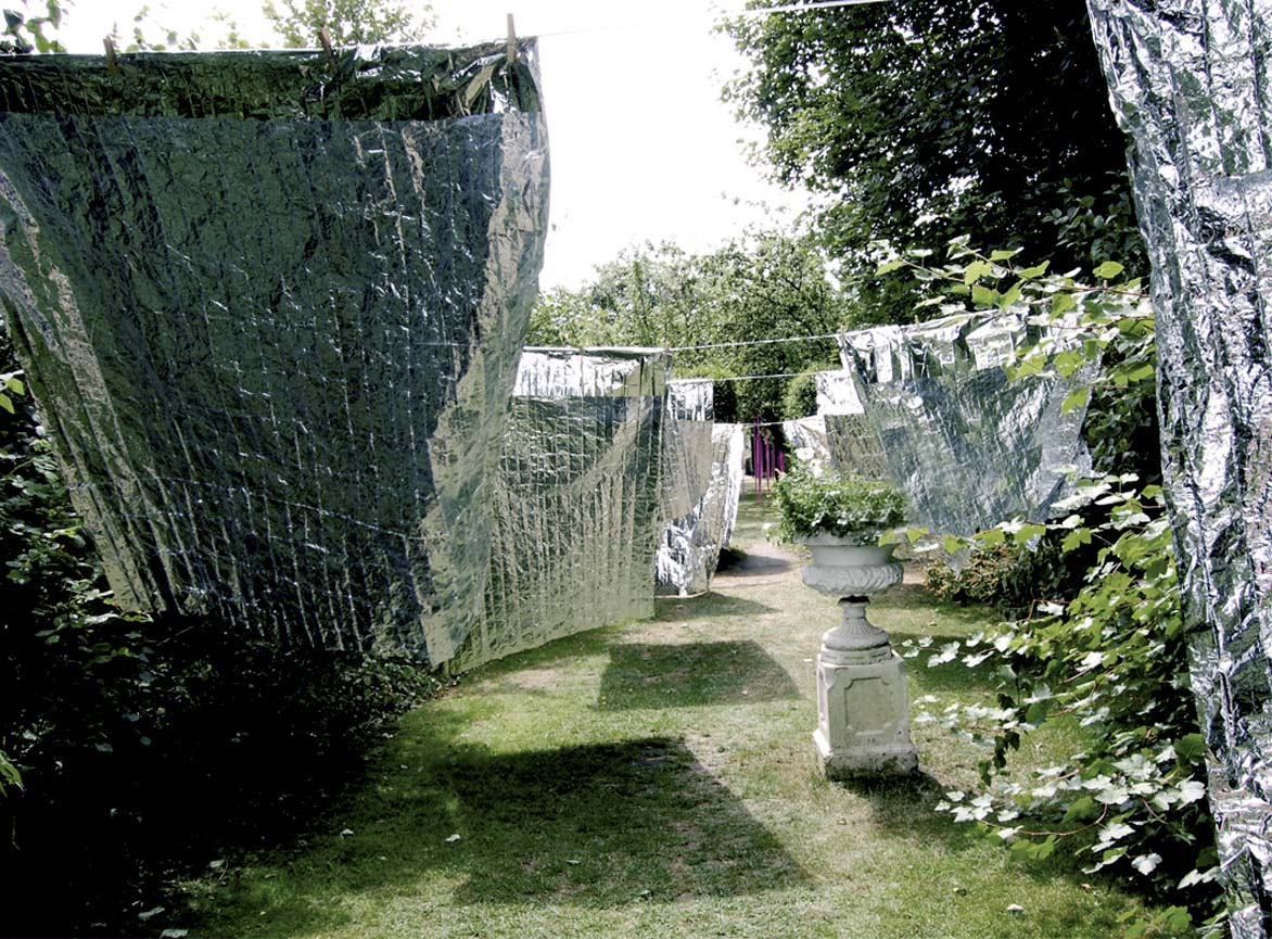 'Laundry Day' Site specific environmental art installation by artist Wendy Hardie which is made of 10 emergency blankets pegged to 5 lengths of silver washing line.